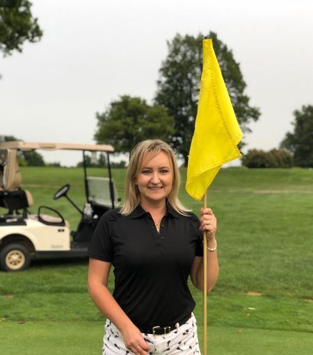 Portrait Of Smiling Woman Holding Yellow Flag While Standing On Golf Course