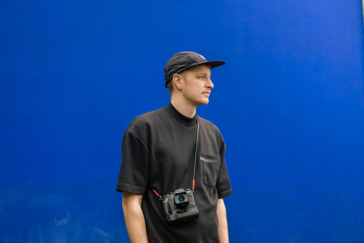 Low angle view of young man wearing cap looking away while standing against blue wall