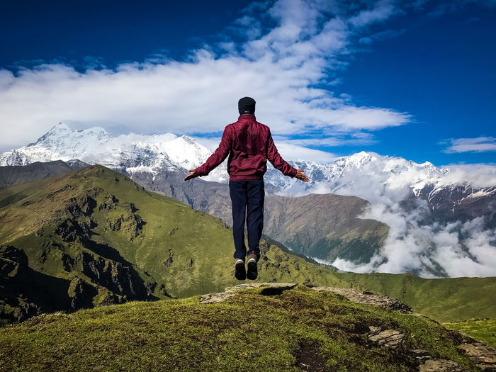 Rear View Of Man Levitating Mountain Against Sky