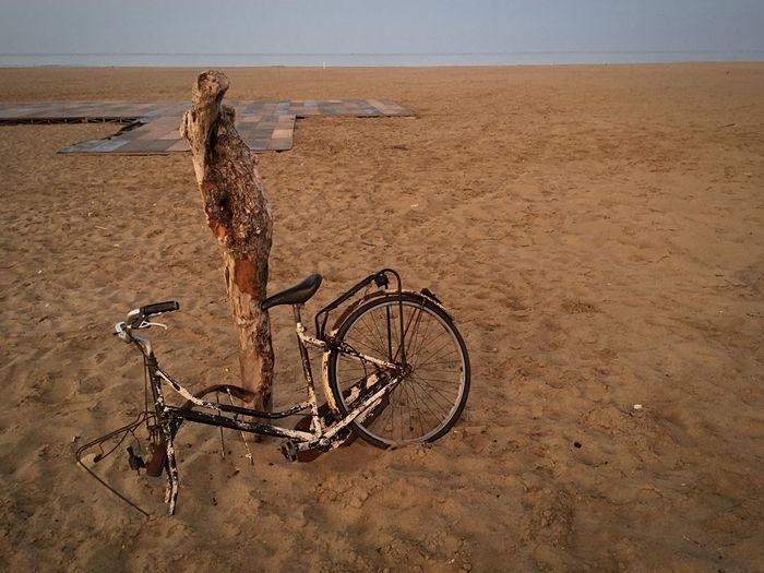 Bicycle on sand at beach against sky