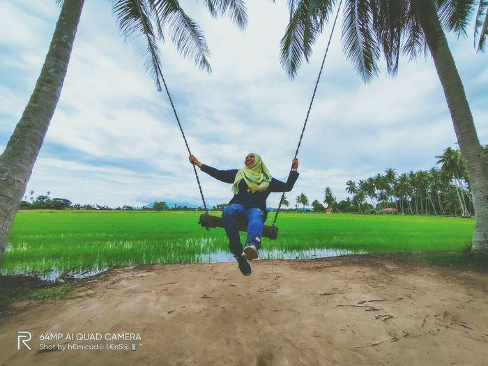 Full length of boy on swing against sky