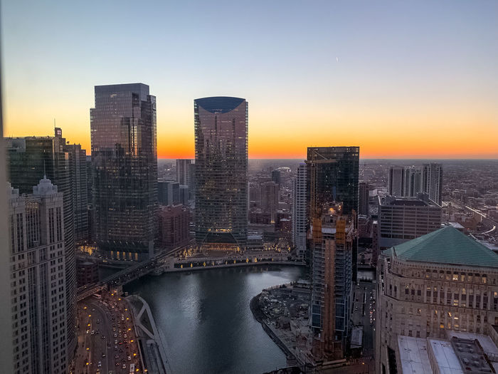 River Amidst Buildings Against Sky During Sunset