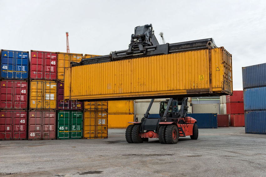 Mobile stacker handler in action at a container terminal. Cargo Container Commercial Dock Container Day Distribution Warehouse Export Freight Transportation Harbor Import Industry Logistic No People Outdoors Shipping  Sky Stack Terminal Transfer Transportation