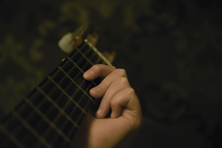 Cropped hand playing guitar against wall