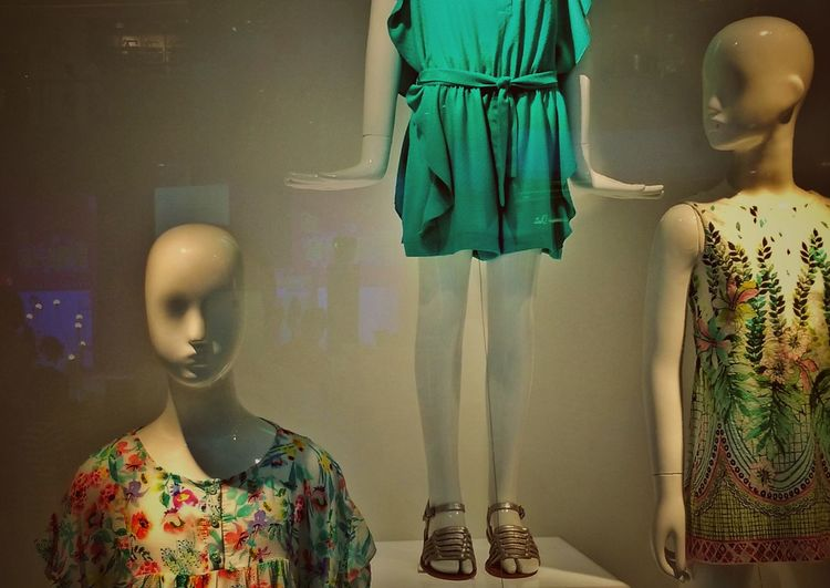 Mannequins seen through store window in shopping mall