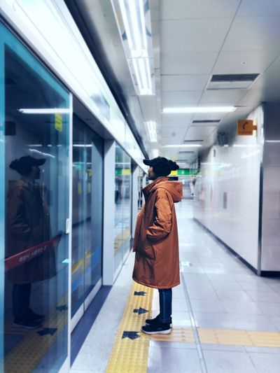 Side view of woman wearing overcoat while standing at illuminated subway