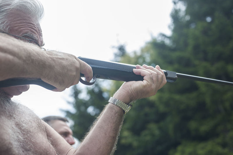 Close-Up Of Senior Man Holding Gun Against Clear Sky