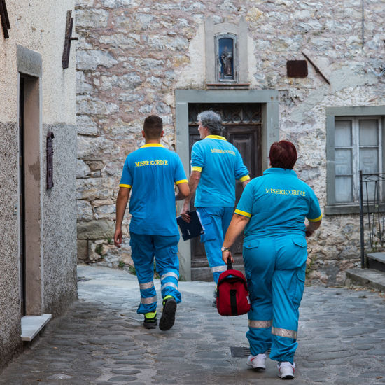 First Aid Helping Adult Ambulance Service Ambulance Staff Architecture Building Building Exterior Built Structure Casual Clothing City Day First-aid Worker Full Length Helloworld Lifestyles Men Outdoors People Real People Rear View Rescue Togetherness Walking Rescue Worker Assisted Living Community Outreach Nurse Volunteer Social Services
