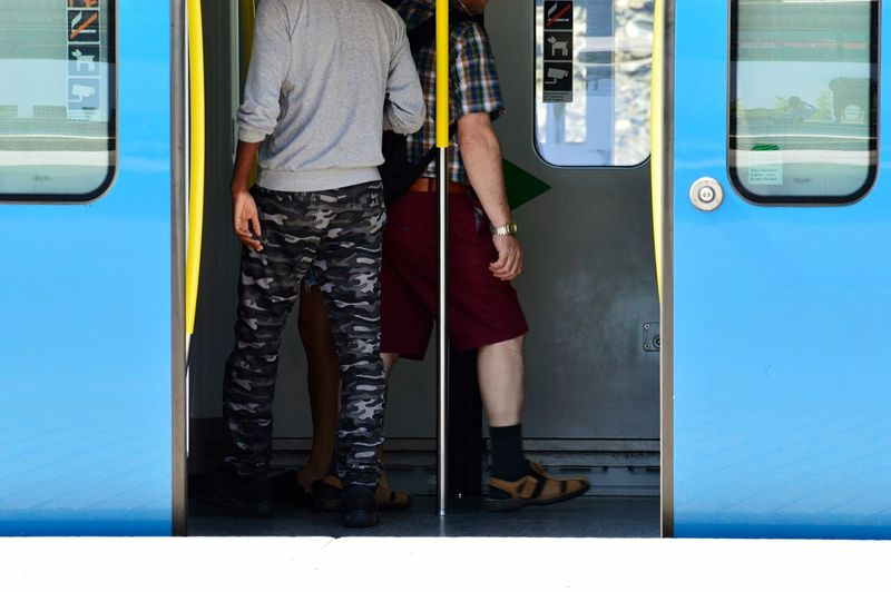 Low section of men standing in train