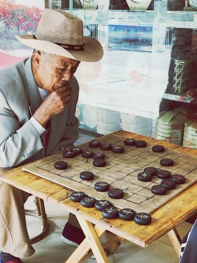 Chinese chess EyeEm Selects Real People One Person Lifestyles Table Leisure Activity Indoors  Hat High Angle View Sitting Relaxation Visual Creativity