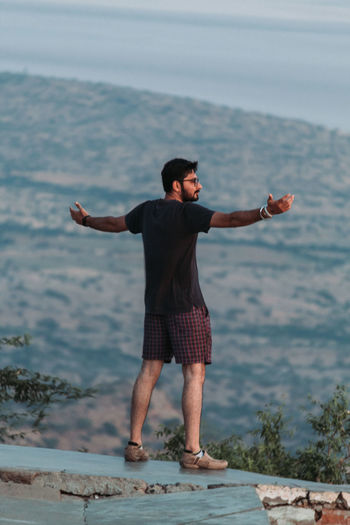 Full length of young man arms outstretched standing on stone wall