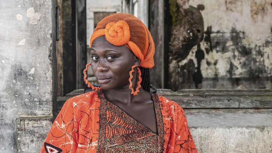 Portrait of woman wearing orange headwear against wall