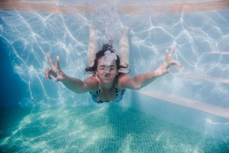 Woman gesturing while swimming underwater in pool