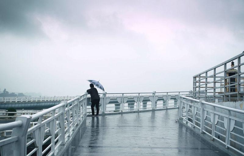 Man With Umbrella Standing On Bridge Against Sky During Rainy Season