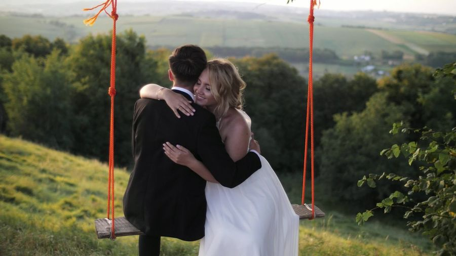 Couple embracing on rope swing at mountain