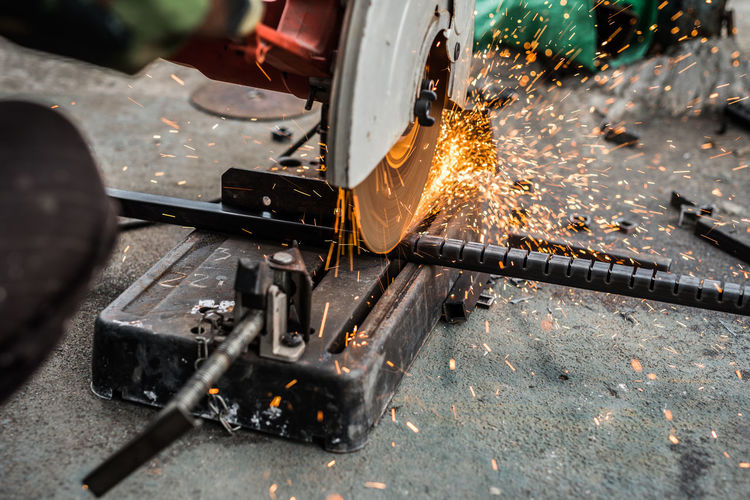 Close-up of grinder cutting metal in factory