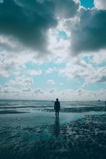 Rear view of silhouette man standing on beach against sky