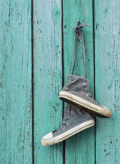 Close-Up Of Shoes Hanging On Green Wooden Fence
