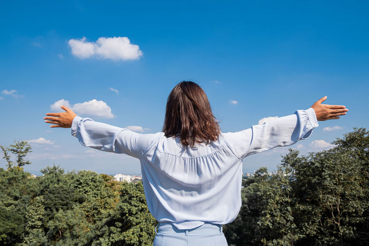 Rear view of woman with arms outstretched standing against sky