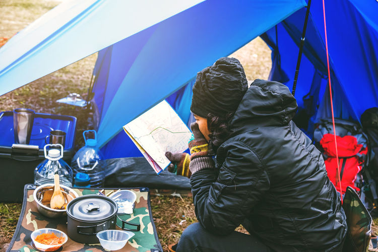 Man sitting on chair at campsite