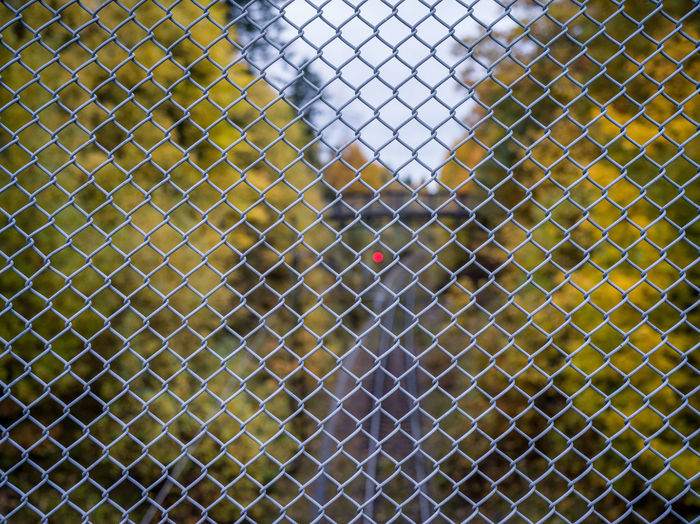 High angle view of chainlink fence on cobblestone