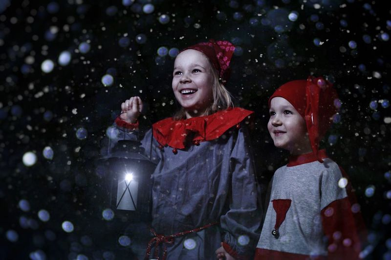 Cheerful siblings holding lantern while standing in snowfall during christmas