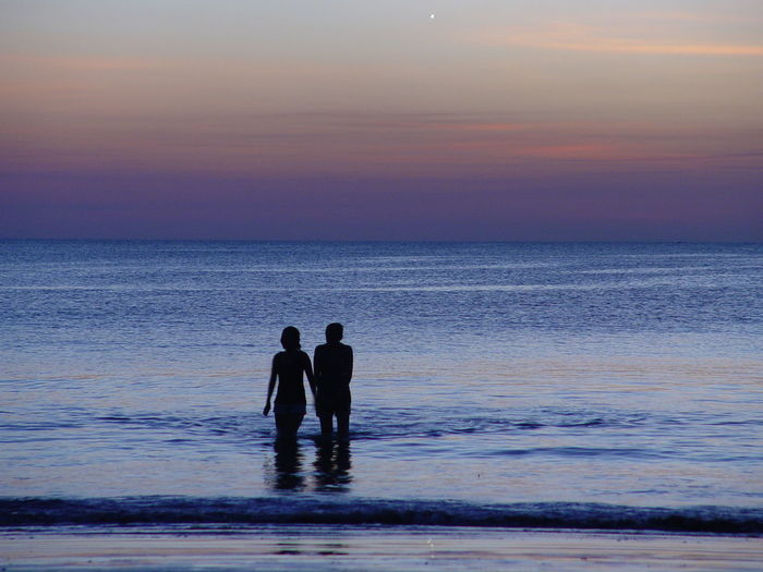 Silhouette people wading in sea against sky during sunset