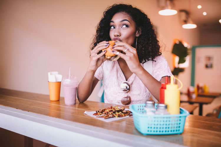 Thoughtful woman eating snack at restaurant
