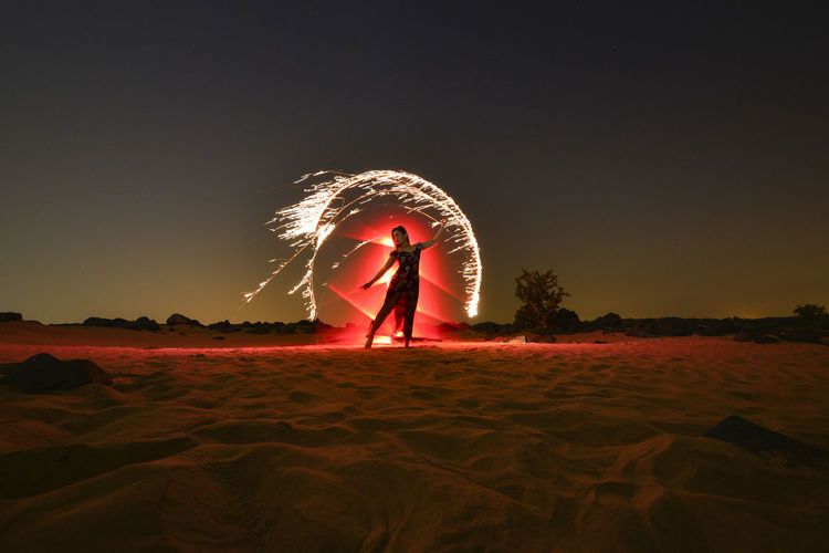 Woman standing at beach against sky at night