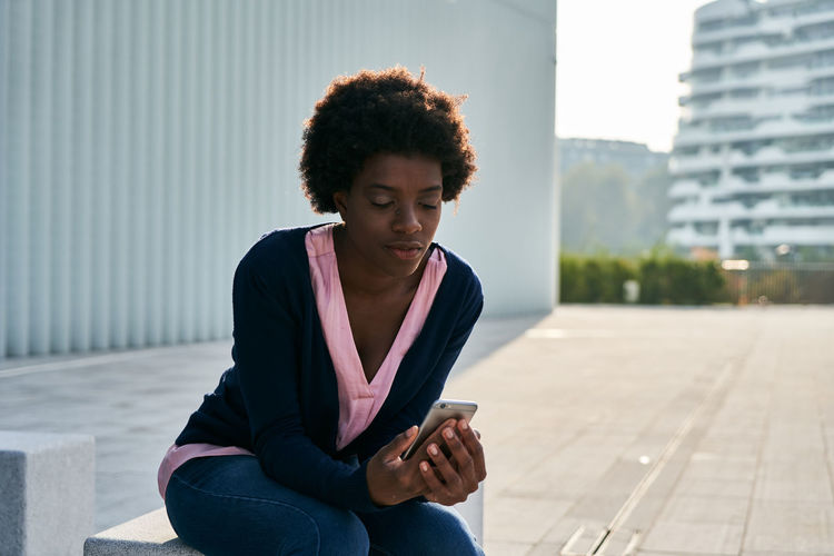 Young woman looking at camera while sitting in city