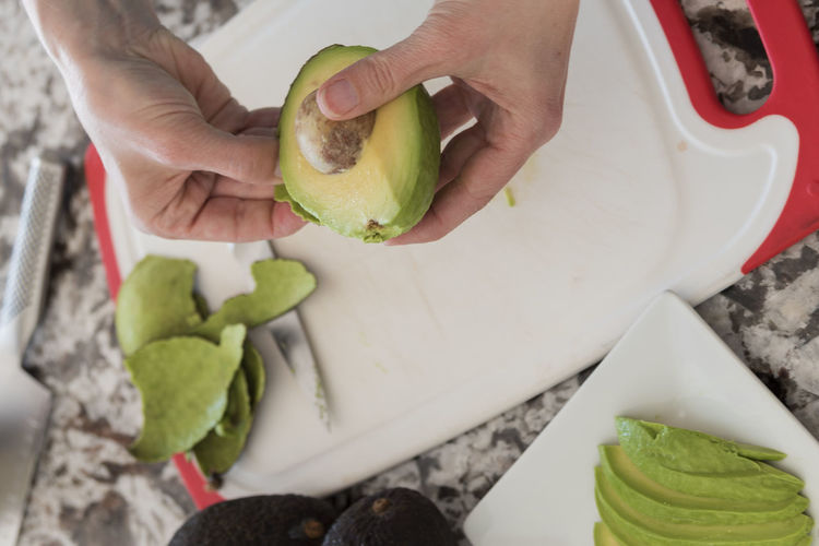 Cropped Image Of Hands Peeling Avocado On Cutting Board