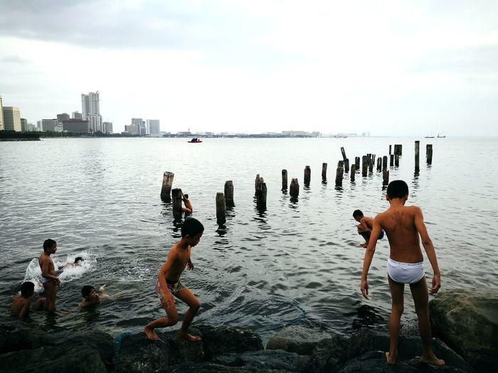 Men standing on riverbank against sky