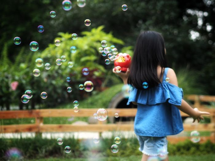 Woman with bubbles in park