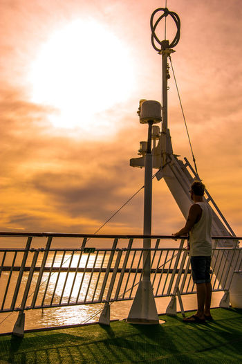 Man standing on cruise ship deck at sea against sky during sunset