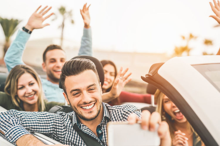 Friends having fun on convertible car Convertible Friends Car Happy People Young Adult Youth Cabriolet Young Men Smiling Happiness Men Emotion Group Of People Adult Togetherness Communication Women Young Women Sitting Enjoyment Lifestyles Portrait Friendship Arms Raised