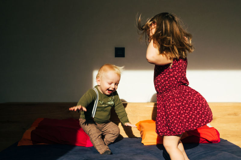 Playful siblings on bed at home
