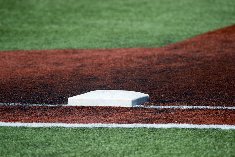 Photograph of first base before a baseball game. Absence Ball Baseball - Sport Baseball Diamond Competition Copy Space Court Day Dividing Line Grass Green Color Land Nature No People Outdoors Plant Playing Field Selective Focus Sport Stadium