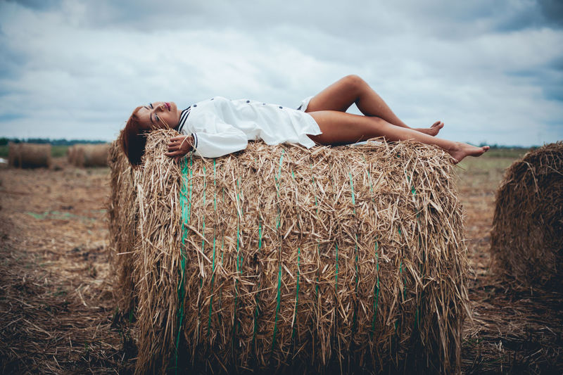 Side view of young woman sleeping on hay bale against cloudy sky at farm