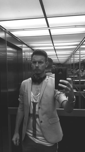 Reflection of man holding smart phone and clicking photograph in lift