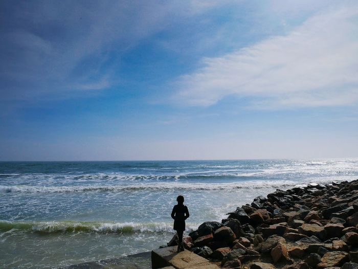Rear view of man on rock at beach against sky