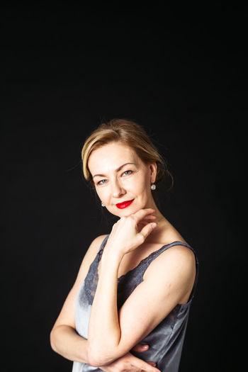 Portrait of smiling mature woman against black background