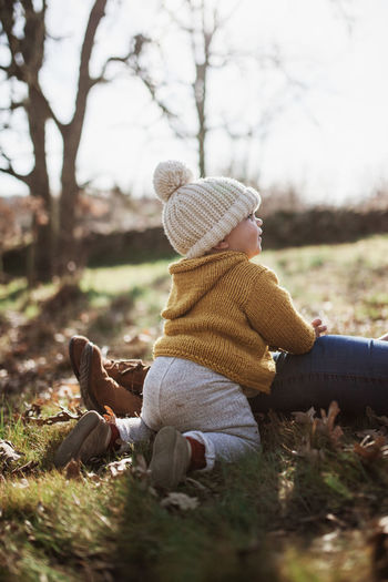Mother and daughter wearing warm clothing while sitting on land