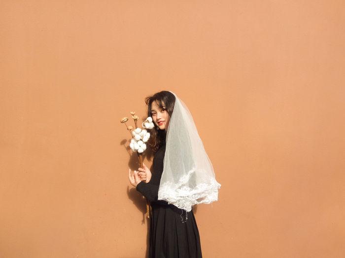 Portrait of bride standing against orange background