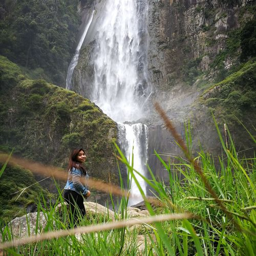 Side view of woman standing by waterfall