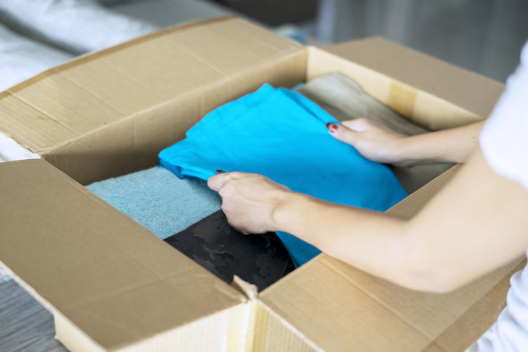 Midsection of woman packing clothes in cardboard box