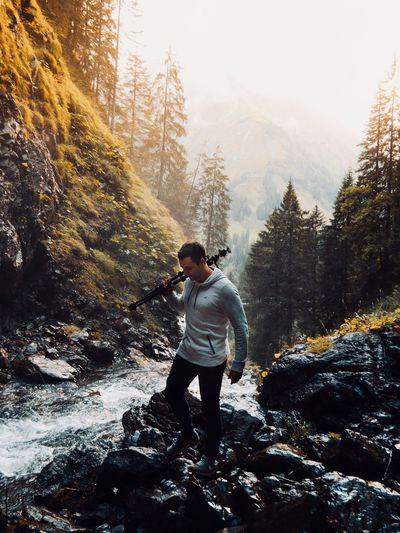 Man walking on rocks by stream at forest