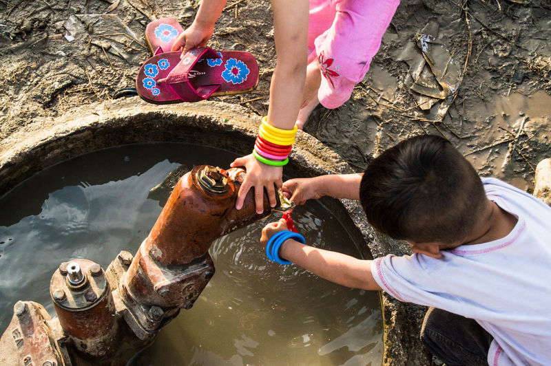 High angle view of boy and girl using water pump