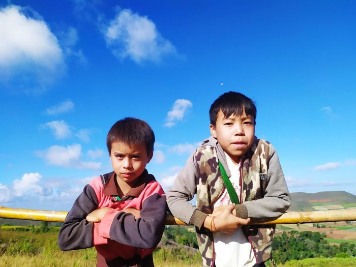 Portrait of brothers standing by bamboo against sky