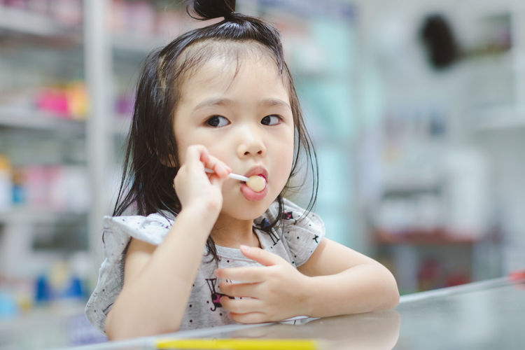 Child Childhood Cute Eating Females Focus On Foreground Food Food And Drink Front View Girls Headshot Holding Indoors  Innocence Looking At Camera Mouth Open One Person Portrait Sweet Food Temptation Women