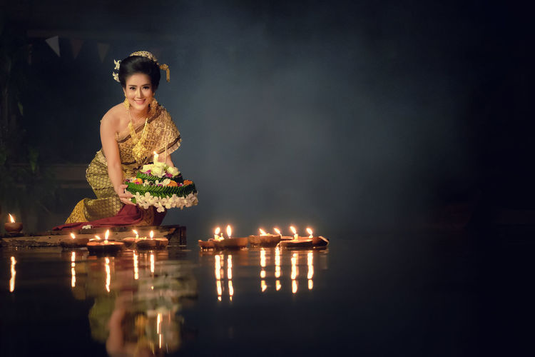 Loy Krathong Traditional Festival, Thai woman hold kratong, Thailand, Asia woman in Thai dress traditional hold kratong and bring Krathong to float in Loi kratong day of Thailand. Adult Adults Only Beautiful Woman Beauty Burning Flame Illuminated Indoors  Looking At Camera Night Oil Lamp One Person One Woman Only One Young Woman Only People Portrait Smiling Standing Table Water Young Adult Young Women